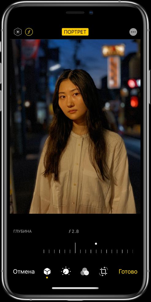 Экран редактирования фотографии, снятой в режиме «Портрет». В левом верхнем углу экрана находится кнопка интенсивности освещения и кнопка регулировки резкости. По центру вверху экрана расположена кнопка режима «Портрет» в положении «Вкл.», а в правом верхнем углу находится кнопка плагинов. По центру экрана показана фотография, под ней расположен бегунок для настройки резкости. Под бегунком слева направо расположены кнопки «Отменить», «Портрет», «Настроить», «Фильтры», «Обрезать» и «Готово».