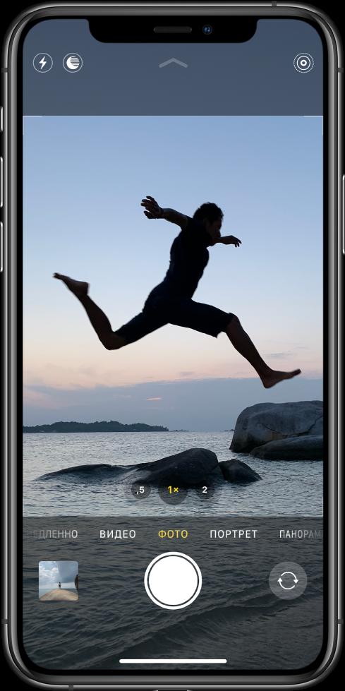 Экран приложения «Камера» в режиме фотографирования; другие режимы отображаются слева и справа под видоискателем. Кнопки вспышки, ночной съемки и LivePhoto отображаются в верхней части экрана. Под режимами камеры расположены (слева направо): миниатюра изображения для открытия фото и видео, кнопка затвора и кнопка переключения камеры.