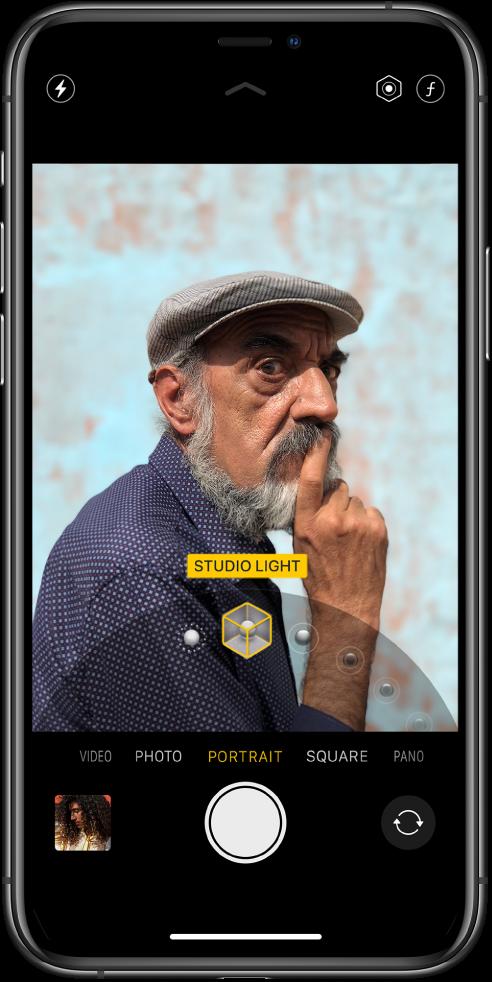 Екран апликације Camera са изабраним режимом Portrait. У приказивачу оквир показује да је опција Portrait Lighting подешена на Studio Light, а приказан је и клизач за промену опције осветљења.