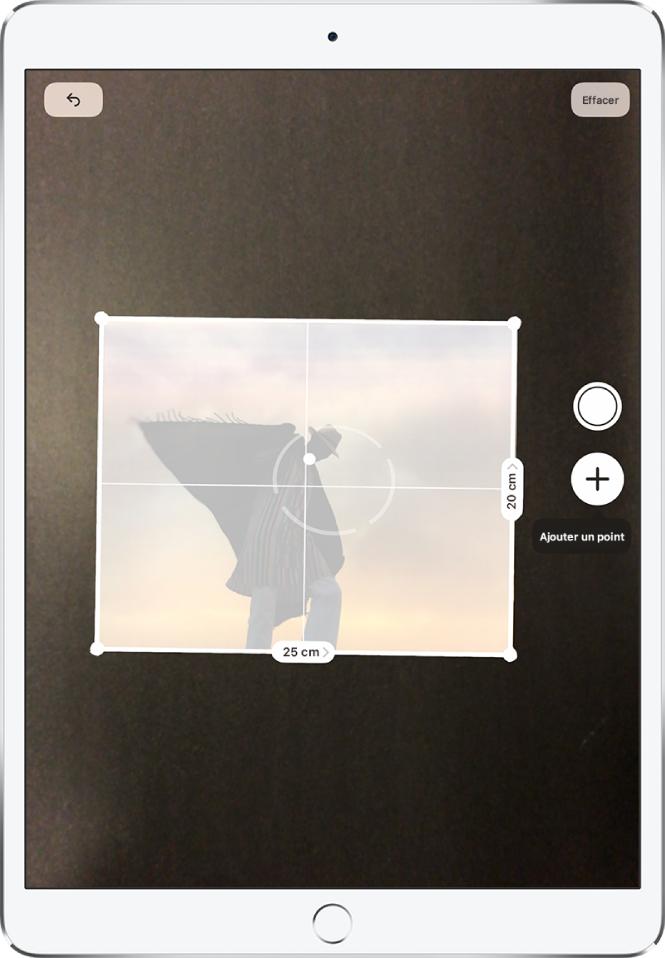 Une photographie papier est mesurée et ses dimensions s'affichent le long de ses bords droit et inférieur. Le bouton Prendre une photo est situé vers le milieu du bord droit.