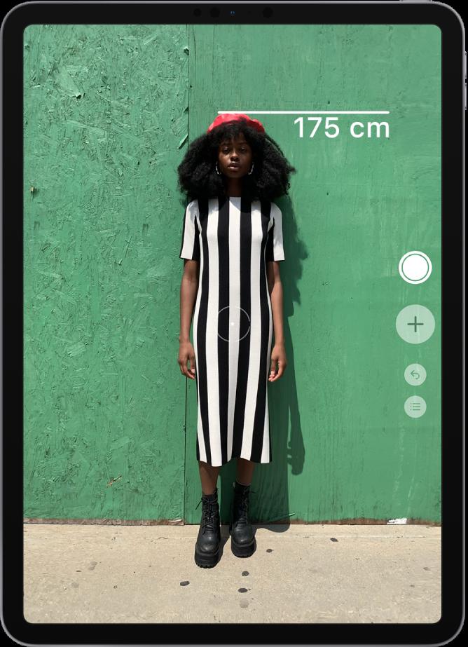 La taille d'une personne est en cours de mesure, avec la mesure de la taille affichée en haut de la tête de la personne. Le bouton «Prendre une photo» est actif sur le bord droit pour prendre une photo de la mesure.