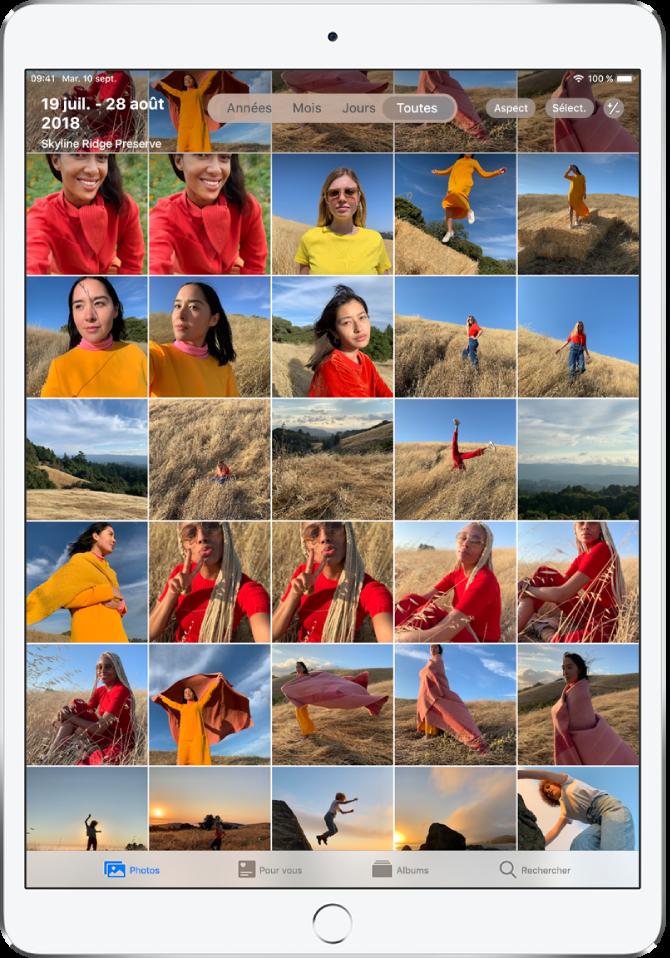 App Photos. En bas de l'écran, de gauche à droite, se trouvent les onglets Photos, Pourvous, Albums et Rechercher. L'onglet Photos est sélectionné et une grille de vignettes de photos remplit l'écran. En haut à gauche de l'écran se trouvent la date et l'emplacement des photos prises. En haut au centre se trouvent les options d'affichage des photos: Années, Mois, Jours et «Toutes les photos»; l'option «Toutes les photos» est sélectionnée. En haut à droite de l'écran se trouvent les boutons Aspect, Sélectionner et Réduire/agrandir.