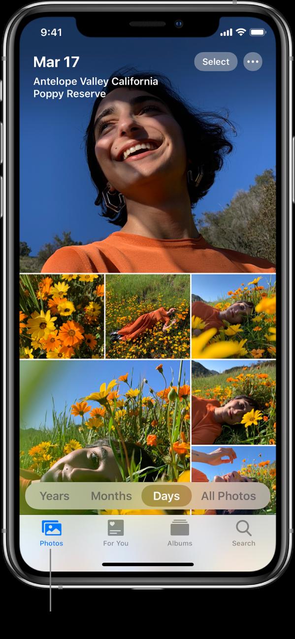 """O app Fotos em um iPhone aberto na aba Fotos com a visualização Dias selecionada. Uma linha aponta para a aba Fotos com a frase de destaque """"Veja fotos e vídeos de qualquer dispositivo com o Fotos do iCloud ativado."""""""