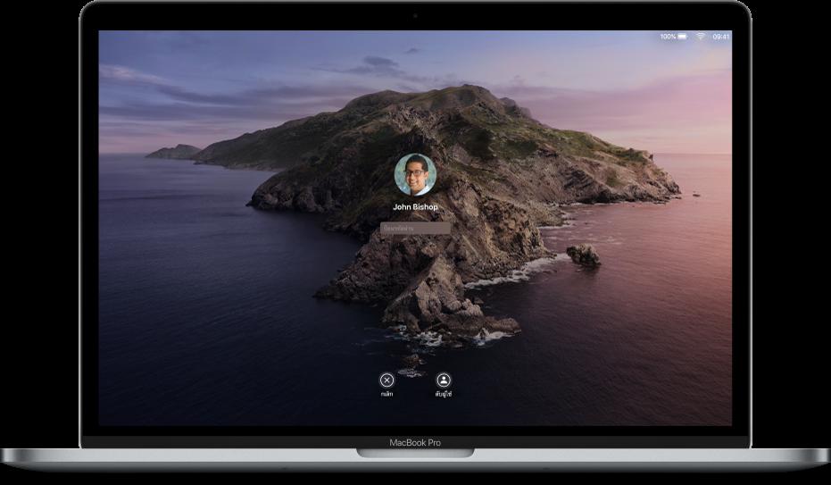 เดสก์ท็อป Mac ที่แสดงหน้าจอเข้าสู่ระบบที่ล็อคอยู่ พร้อมกับช่องรหัสผ่านที่กึ่งกลางและปุ่มยกเลิกที่ด้านล่างสุด