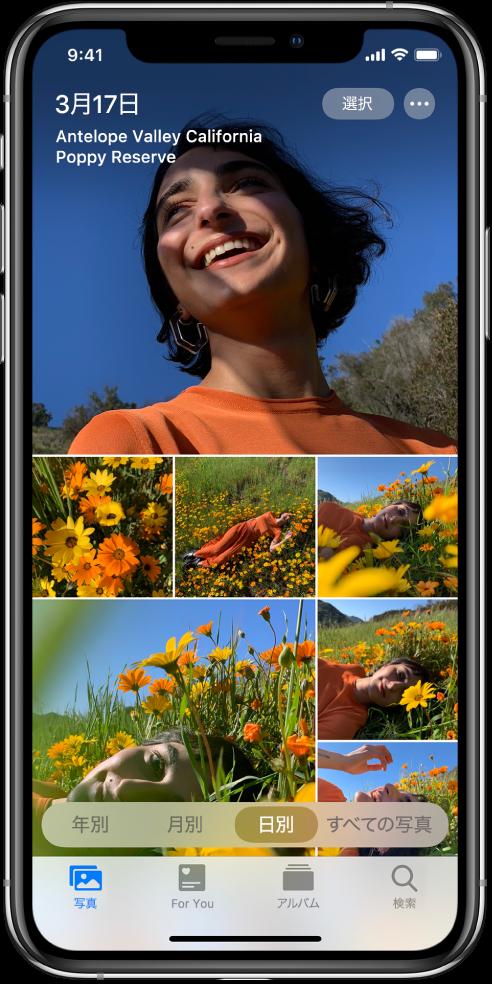 「日別」表示で表示されているフォトライブラリ。日付で選ばれた写真のサムネールが画面いっぱいに表示されています。画面の左上には写真の撮影日と撮影地が表示されています。右上には「選択」ボタンとその他のオプションボタンがあります。「選択」をタップして写真を共有したり、その他のオプションボタンをタップして写真の詳細を表示したりできます。サムネールの下には、「年別」、「月別」、「日別」、「すべての写真」というフォトライブラリの表示オプションがあります。下部には、「写真」、「For You」、「アルバム」、および「検索」タブがあります。