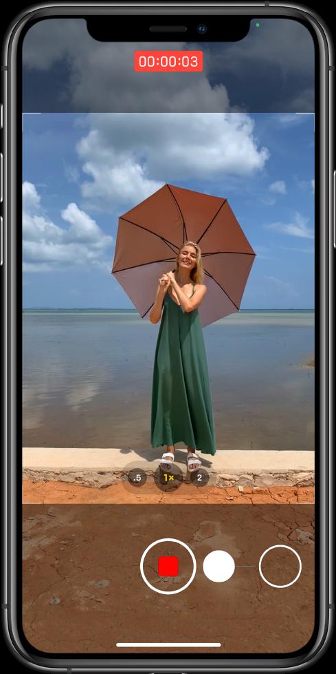 Obrazovka fotoaparátu se znázorněním pohybu pro spuštění nahrávání videa QuickTake. Udolního okraje displeje se tlačítko Spoušť přesouvá doprava ktlačítku uzamknutí aje zde znázorněno gesto spuštění videa QuickTake vrežimu Foto. Uhorního okraje displeje je vidět ukazatel času záznamu
