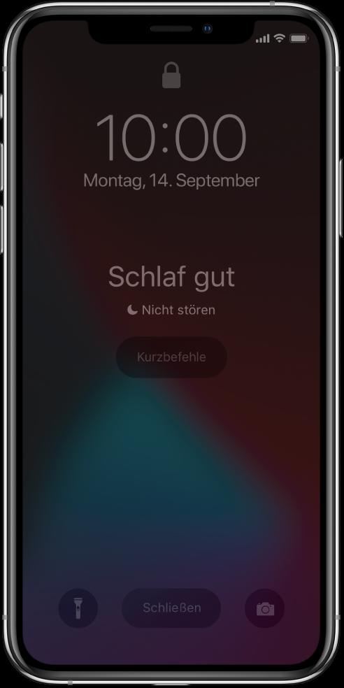 """In der Mitte des iPhone-Bildschirms wird """"Schlaf gut"""" und """"Nicht stören"""" angezeigt. Darunter befindet sich die Taste """"Kurzbefehle"""". Unten auf dem Bildschirm befinden sich von links nach rechts die folgenden Tasten: """"Taschenlampe"""", """"Schließen"""" und """"Kamera""""."""