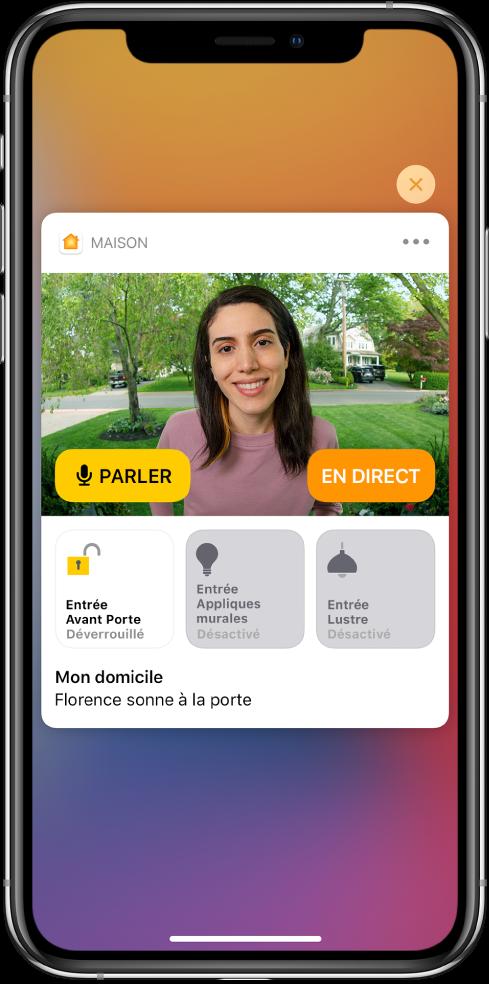 Une notification de Maison est affichée sur l'écran de l'iPhone. Elle montre la photo d'une personne à la porte d'entrée avec un bouton Parler sur la gauche. Des boutons d'accessoires pour les lumières de la porte d'entrée et de l'entrée se trouvent en dessous, avec les mots «Ashley sonne à la porte». Un bouton Fermer apparaît en haut à droite de la notification.