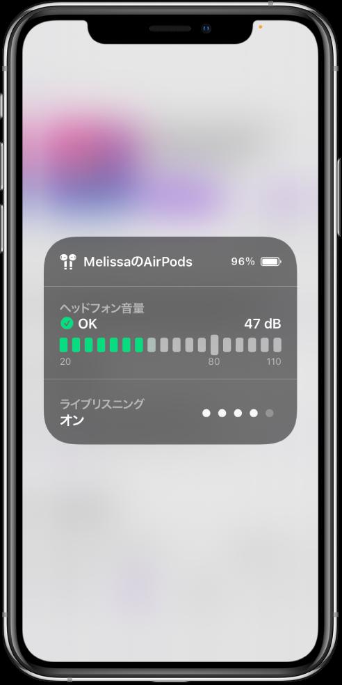 スクリーン上に重なって表示されたカード。カードには、AirPodsの音量のグラフが表示されています。グラフには47デシベルと表示されており、「OK」の文字が出ています。グラフの下には、「ライブリスニング」が「オン」と表示されています。「ライブリスニング」の音量は、5つの点のうち4つが光って表示されています。