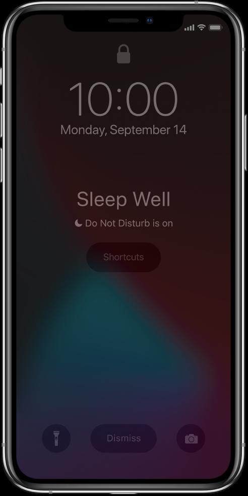 Ортасында «Sleep Well» және «Do Not Disturb is on» хабарларын көрсетіп тұрған iPhone экраны. Оның астындағы — Shortcuts түймесі. Экранның төменгі жағында солдан оңға қарай — Flashlight, Dismiss және Camera түймелері.