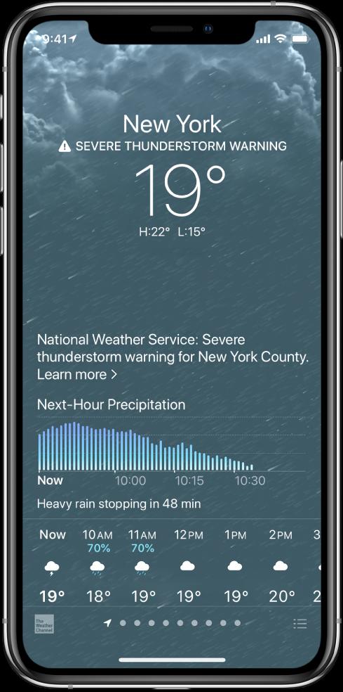 Lietotnes Weather ekrānā no augšas uz leju redzama: atrašanās vieta, brīdinājums par spēcīgu pērkona negaisu, pašreizējā temperatūra, dienas augstākā un zemākā temperatūra un grafiks, kurā redzams nākamās stundas nokrišņu līmenis. Ekrāna apakšā ir laika prognoze pa stundām; zem tās ir redzama punktu rinda, kas norāda uz atrašanās vietu skaitu sarakstā. Apakšējā labajā stūrī atrodas poga Edit Cities.
