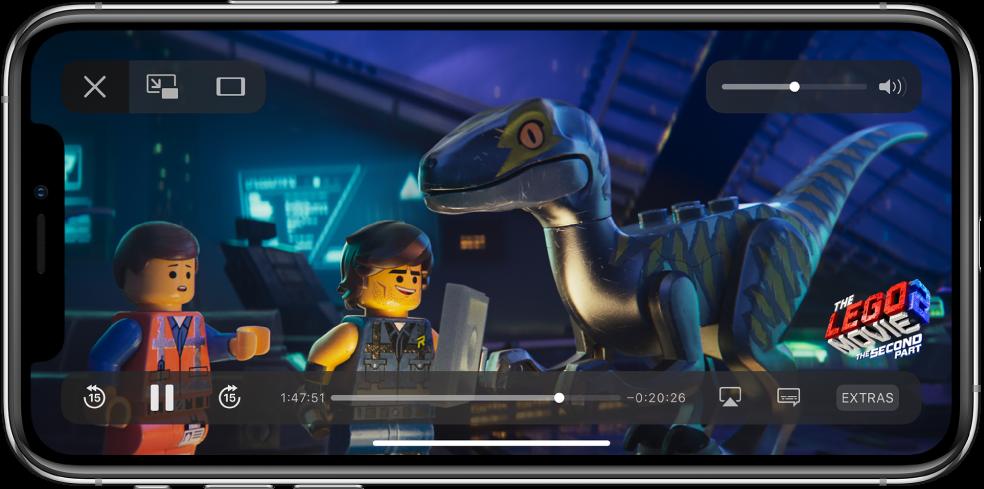 Predvajanje filma s prikazovanjem kontrolnikov predvajanja. Gumba »Done« in »Scale to Fill« sta zgoraj levo. Drsnik za jakost zvoka je zgoraj desno. Spodaj levo so gumbi za preskok 15 sekund nazaj, začasno zaustavitev in preskok 15 sekund naprej. Na sredini spodaj je drsnik, s katerim lahko prilagodite odsek videoposnetka. Ob straneh drsnika so prikazani podatki o pretečenem času in preostalem času. Spodaj desno so prikazani gumbi za spremembo mesta videoposnetka, prikaz podnapisov in predvajanje dodatne vsebine.