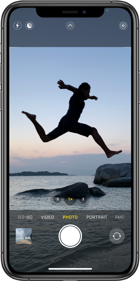Màn hình Camera ở chế độ Ảnh, với các chế độ khác ở bên trái và phải bên dưới kính ngắm. Các nút cho Flash, chế độ Ban đêm, Điều khiển camera và Live Photo xuất hiện ở đầu màn hình. Bên dưới các chế độ camera, từ trái sang phải, là nút Trình xem ảnh và video, nút Chụp ảnh và nút Chọn camera mặt sau.