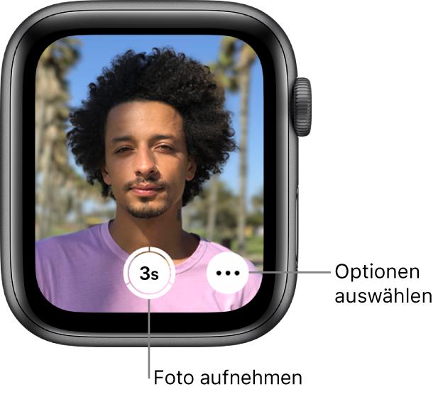 """Die AppleWatch wird als Kamerafernbedienung verwendet. Auf dem Display ist das Kamerabild des iPhone zu sehen. Die Taste """"Bild aufnehmen"""" befindet sich unten in der Mitte und die Taste """"Weitere Optionen"""" rechts davon. Wenn du ein Foto aufgenommen hast, befindet sich unten links die Taste zum Anzeigen des Fotos."""
