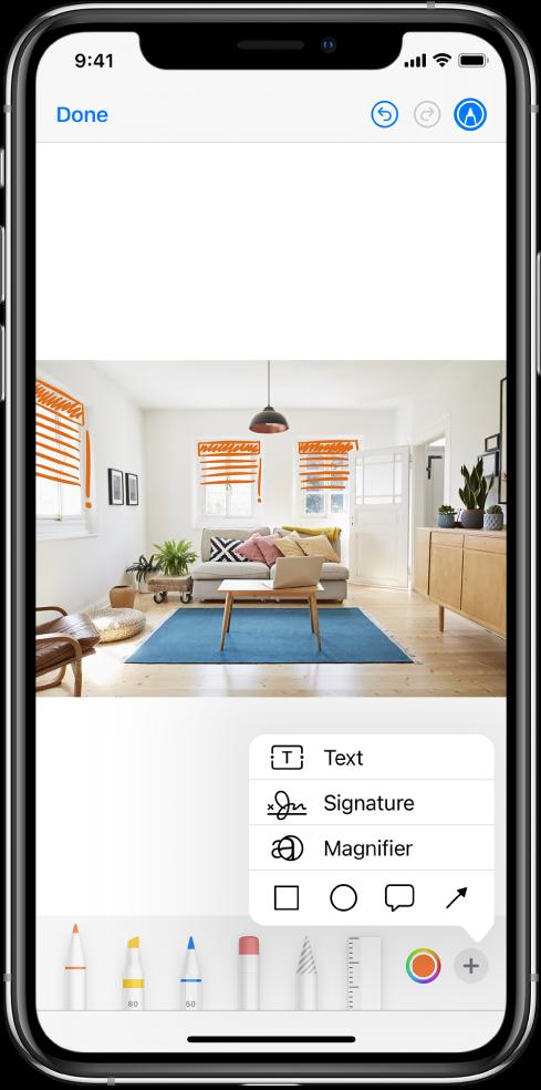 На фотографію нанесено оранжеві лінії, що позначають жалюзі на вікнах. Панель інструментів Розмітки з інструментами для малювання та селектор кольорів, що відображається внизу екрана. Меню з кнопками для додавання тексту, підпису та фігур, а також лупою відображаються в правому нижньому куті.