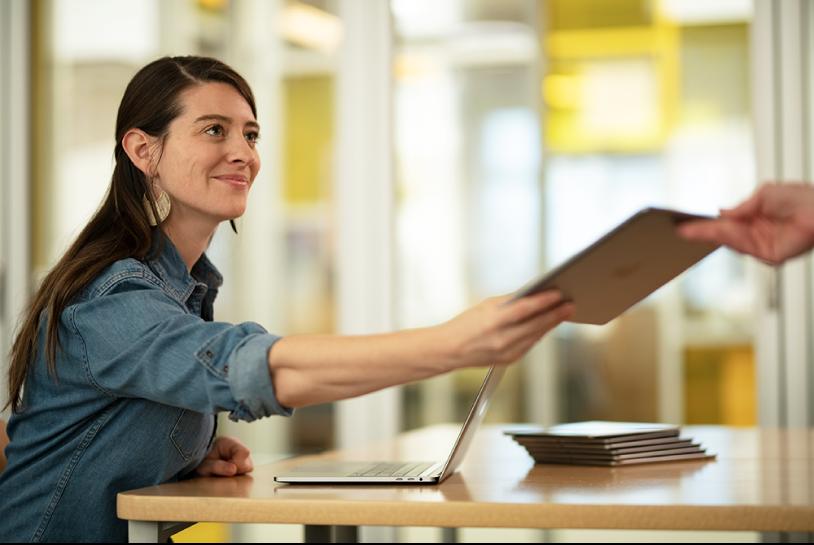 Een vrouwelijke leerkracht zit achter een bureau in een klaslokaal en werkt op een Mac-laptop, er er ligt een stapel iPads op het bureau. Ze geeft een iPad aan een leerling.