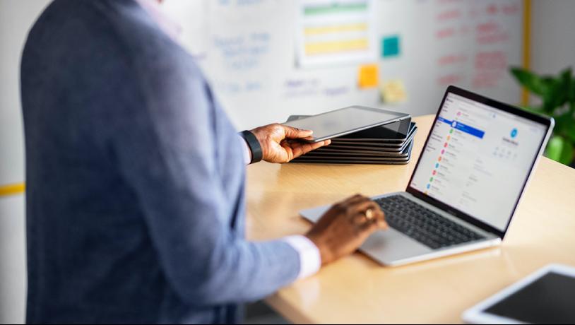 Een vrouw zit achter een bureau en werkt op een Mac-laptop, en er ligt een stapel iPads op het bureau.