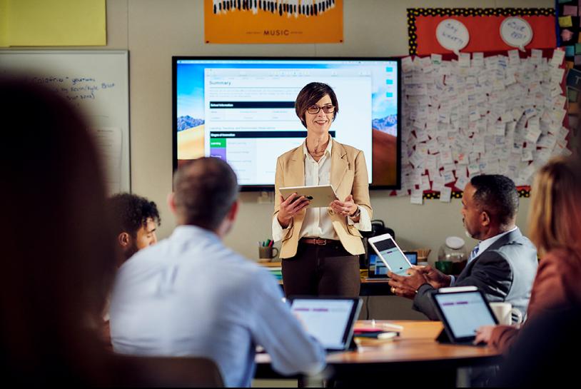 Stojąca kobieta, przedstawiająca informacje ziPada grupie osób uczestniczących wzajęciach kształcenia zawodowego, którzy mają przed sobą otwarte laptopy Mac.