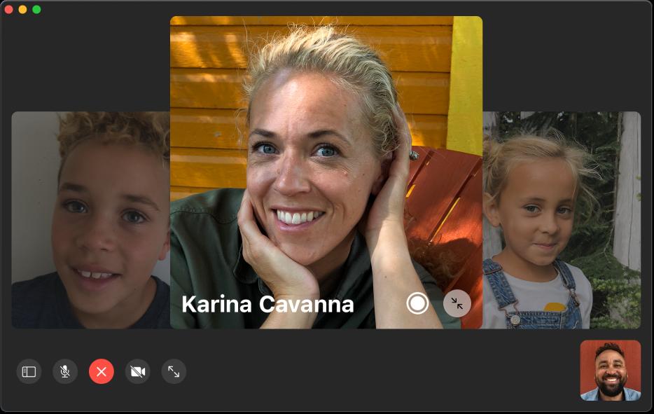 Het FaceTime-venster tijdens een groepsgesprek. In een tegel rechtsonder wordt de persoon weergegeven die het gesprek heeft geïnitieerd. In een grote tegel in het midden van het venster wordt een deelnemer weergegeven, met in het midden van de tegel een Live Photo-knop waarop bellers kunnen klikken om het moment vast te leggen.