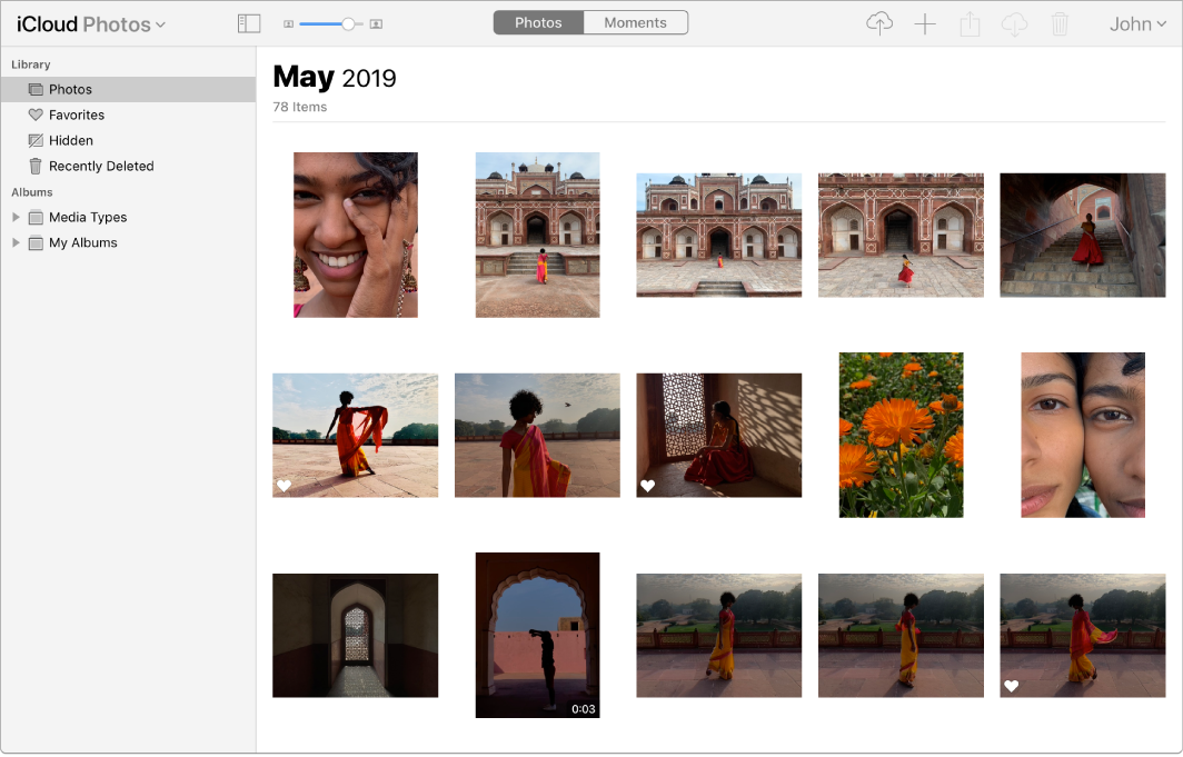 The Photos app on iCloud.com. Photos is selected in the sidebar and photos from May 2019 are visible.