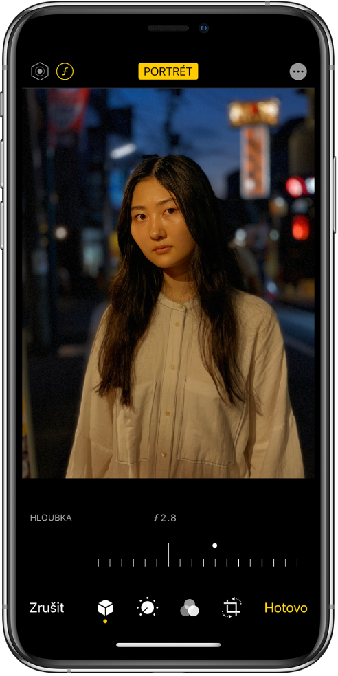 Obrazovka Úpravy sfotkou pořízenou vrežimu Portrét. Vlevo nahoře je na obrazovce vidět tlačítko pro nastavení intenzity osvětlení atlačítko pro doladění hloubky ostrosti. Uprostřed horního okraje obrazovky se nachází zapnuté tlačítko Portrét avpravo nahoře tlačítko Plug-iny. Fotka se zobrazuje uprostřed displeje; jezdcem pod ní můžete měnit nastavení hloubky ostrosti. Pod jezdcem jsou zleva doprava umístěná tlačítka Zrušit, Portrét, Úpravy, Filtry, Ořez aHotovo.