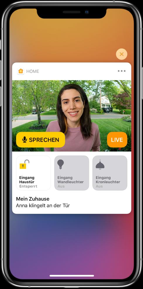 """Eine Mitteilung der App """"Home"""" auf dem Bildschirm des iPhone. Sie zeigt das Bild einer Person, die vor der Tür steht. Links befindet sich eine Sprechtaste. Darunter befinden sich Gerätetasten für die Eingangstür und die Beleuchtung des Zugangsbereichs. Unter den Gerätetasten wird z.B. der Text """"Marion klingelt"""" angezeigt. Oben rechts neben der Mitteilung befindet sich die Taste """"Schließen""""."""