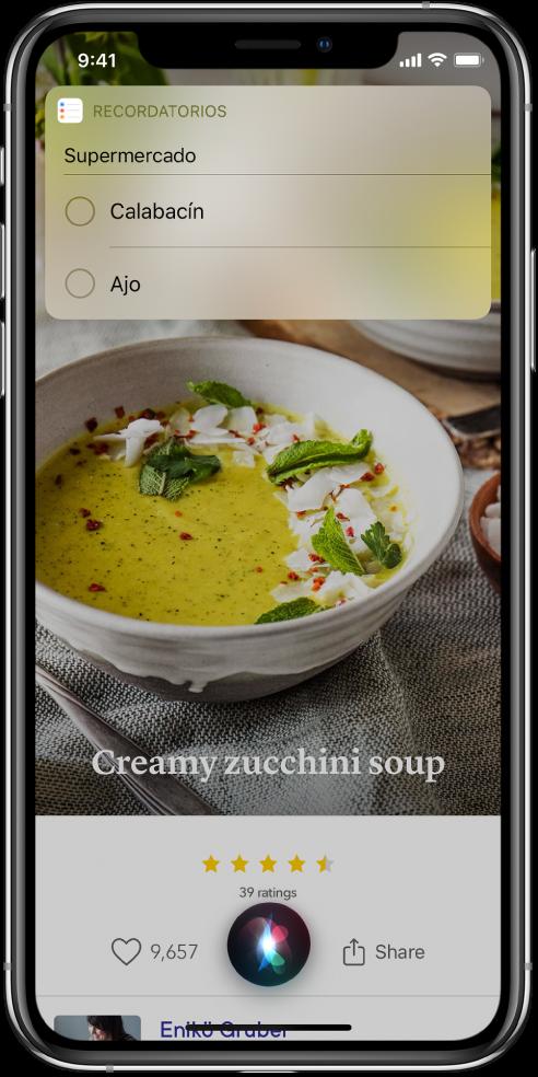 """En respuesta a la petición """"Añade calabacines y ajo a la lista de la compra"""", Siri muestra una lista de recordatorios llamado Compra en la que se ha añadido calabacines y ajo. La lista aparece sobre una receta de crema de calabacín."""