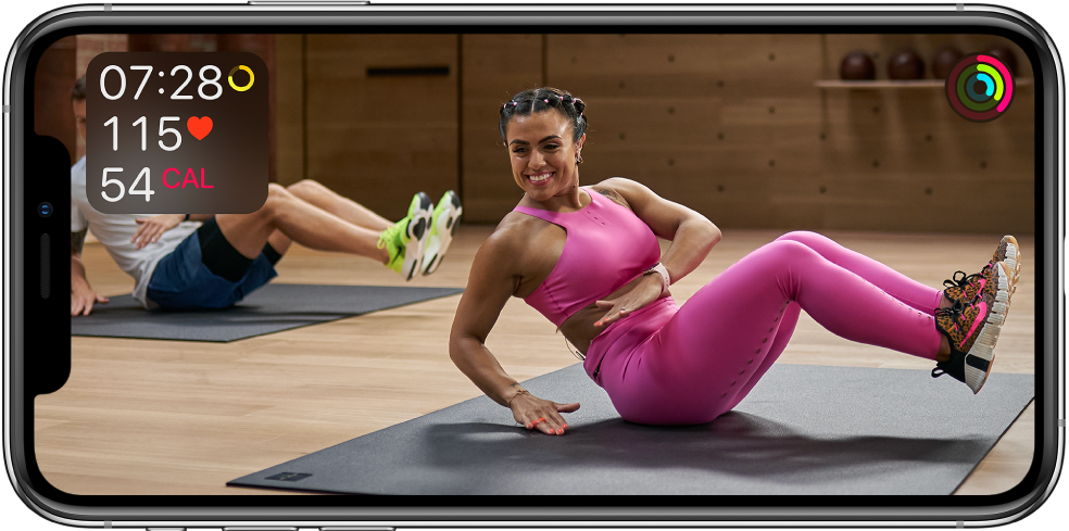 トレーナーが指導するApple Fitness+のワークアウトが表示されている画面。左上にワークアウトの時間、心拍数、および消費カロリーが表示されます。右上にムーブ、エクササイズ、スタンドゴールのリングの進捗が表示されます。