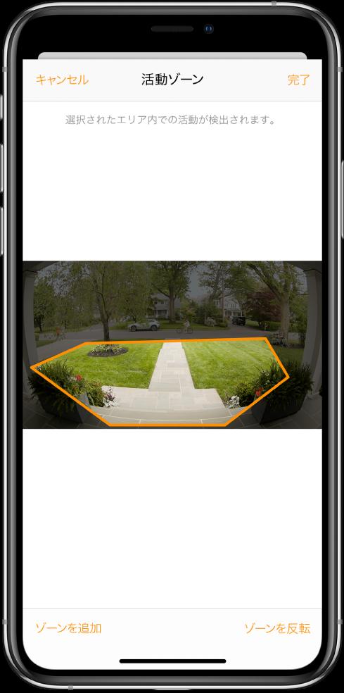 iPhoneの画面。ドアベルのカメラで撮影された画像内の活動ゾーンが表示されています。この活動ゾーンは玄関先と通路を網羅していますが、車道と私道は除外されています。画像の上には「キャンセル」ボタンと「完了」ボタンがあります。下には「ゾーンを追加」ボタンと「ゾーンを反転」ボタンがあります。