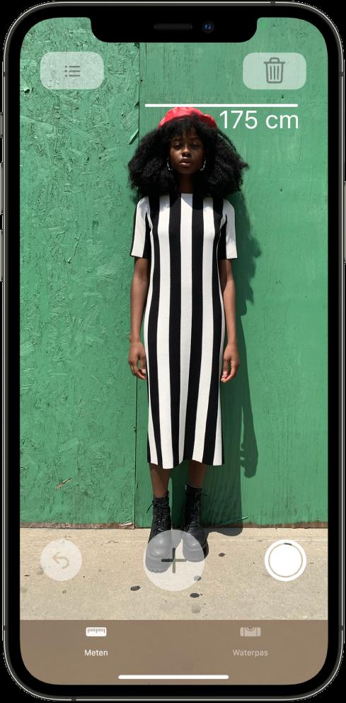 Iemands lengte wordt gemeten, waarbij de lengte boven het hoofd wordt weergegeven. De knop 'Maak foto' is actief aan de rechterkant, zodat je een foto van de meting kunt maken. Rechtsboven zie je de groene indicator dat de camera in gebruik is.
