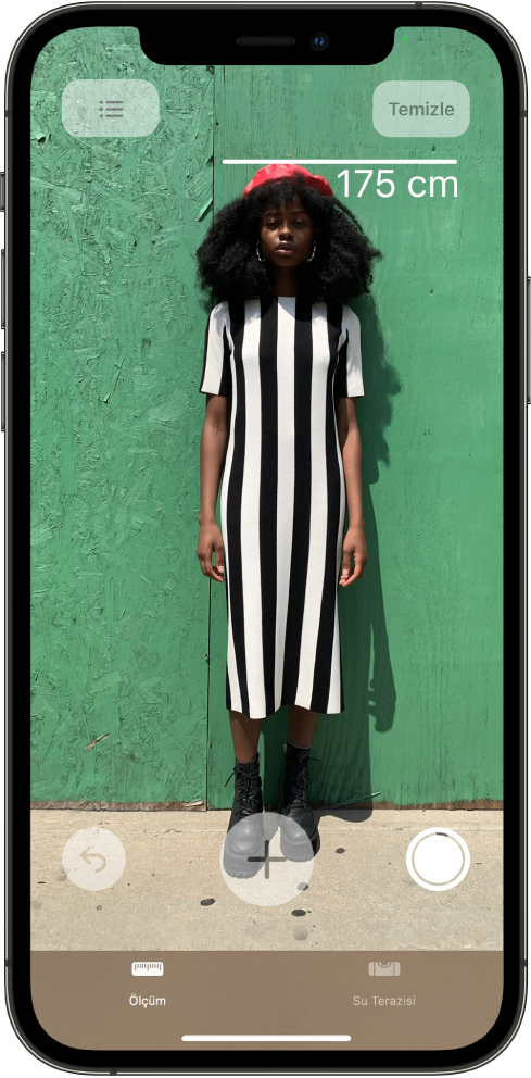 Kişinin boyu ölçülüyor; boy ölçümü kişinin başının üst tarafında gösteriliyor. Ölçümün resmini çekmek için sağ kenarda Resim Çek düğmesi etkin. Sağ üstte, yeşil Kamera Kullanımda göstergesi görünüyor.