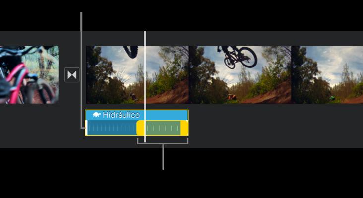 Un intervalo de velocidad con manijas de intervalo amarillas en un clip de audio en la línea de tiempo y con líneas amarillas en el clip que indican los bordes de intervalo.