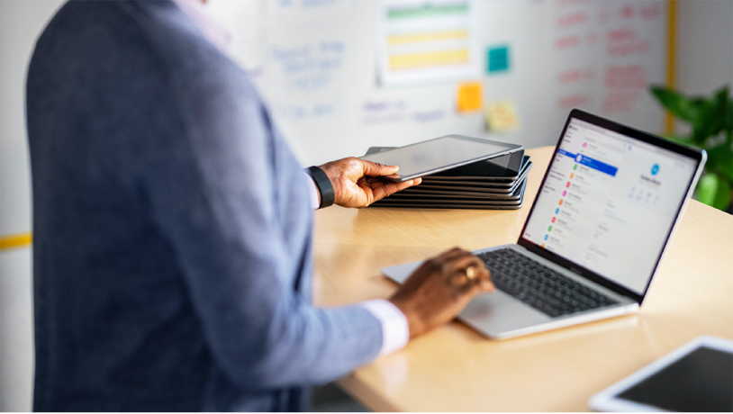Μια γυναίκα στο γραφείο της, που εργάζεται σε ένα φορητό Mac, με μια στοίβα από iPad δίπλα.