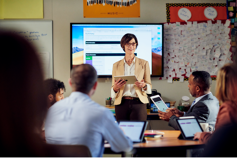 A woman standing and presenting information from an iPad to a group of professionals who have their Mac laptops open in front of them.