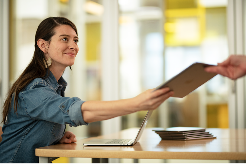 Una donna seduta alla scrivania in classe, con un portatile Mac aperto e accanto a una pila di iPad. Sta distribuendo un iPad a uno studente.