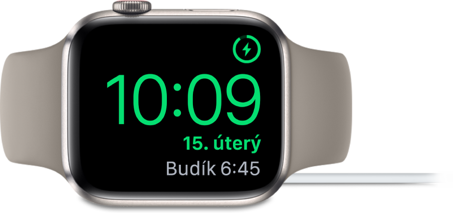 Hodinky AppleWatch položené na boku apřipojené knabíječce; na obrazovce se vpravém horním rohu ukazuje symbol nabíjení, pod ním aktuální čas anejbližší nastavený čas buzení.