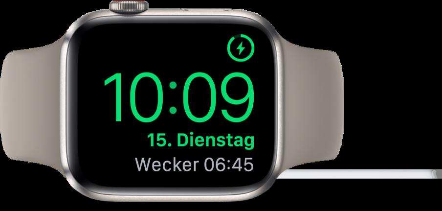 Eine auf die rechte Seite gedrehte AppleWatch, an die das Ladegerät angeschlossen ist und auf deren Display oben rechts das Ladesymbol, darunter die aktuelle Uhrzeit und die Uhrzeit für den nächsten Wecker angezeigt werden.