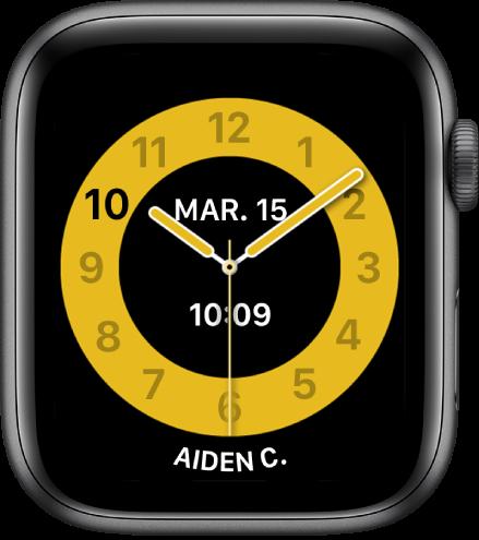 Cadran Mode École, affichant une horloge analogique avec la date vers le haut et l'heure en dessous. Le nom de la personne qui utilise l'AppleWatch se trouve en bas.