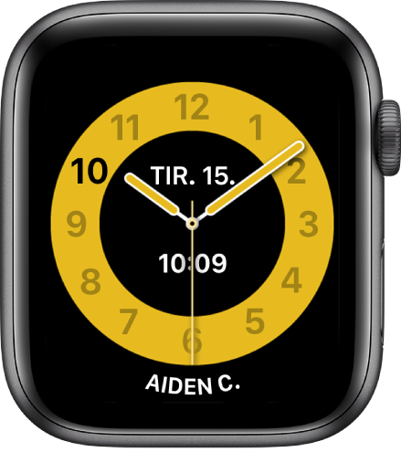 Skoletid-urskiven med en analog klokke med datoen nesten øverst og klokkeslettet under. Nederst er navnet på personen som bruker klokken.