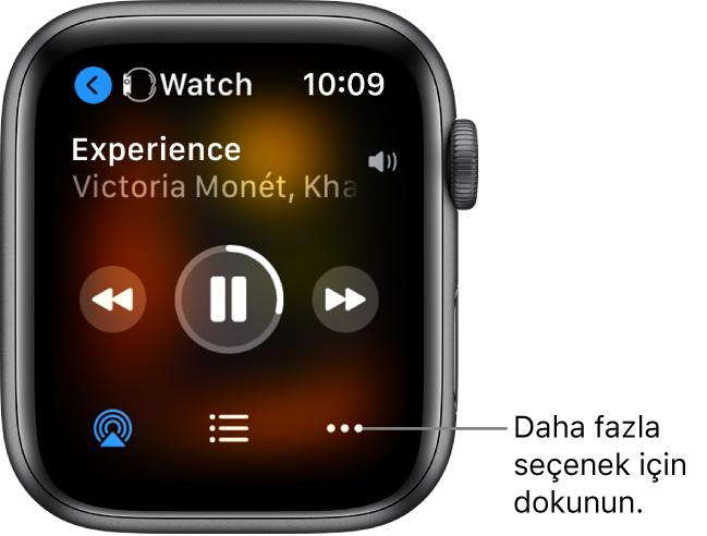 Sizi aygıt ekranına götüren solu gösteren bir ok ile üstte Watch'u gösteren Şu An Çalınan ekranı. Parça başlığı ve sanatçı adı aşağıda görünür. Çalma denetimleri ortadadır. AirPlay, parça listesi ve Daha Fazla Seçenek düğmeleri en alttadır.