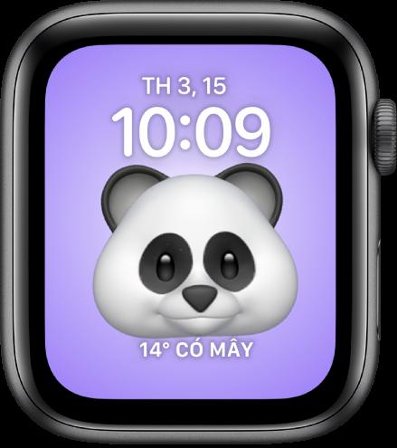 Mặt đồng hồ Memoji, là nơi bạn có thể điều chỉnh nhân vật Memoji và một tổ hợp ở dưới cùng. Chạm vào màn hình để tạo hiệu ứng cho Memoji. Ngày và giờ nằm ở trên cùng và tổ hợp Thời tiết ở dưới cùng.