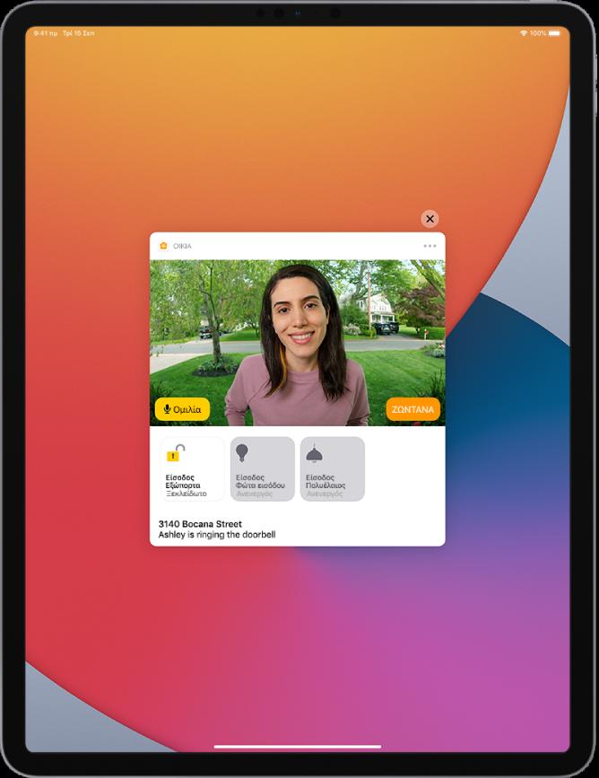 Στην οθόνη του iPad εμφανίζεται μια γνωστοποίηση από την Οικία. Φαίνεται η εικόνα ενός ατόμου στην εξώπορτα με ένα κουμπί «Ομιλία» στα αριστερά. Παρακάτω βρίσκονται κουμπιά αξεσουάρ για την εξώπορτα και τα φώτα της εξώπορτας. Κάτω από τα κουμπιά αξεσουάρ εμφανίζονται η διεύθυνση οικίας και οι λέξεις «Η Γιάννα χτυπά το κουδούνι της πόρτας». Ένα κουμπί «Κλείσιμο» εμφανίζεται στην πάνω δεξιά πλευρά της γνωστοποίησης.