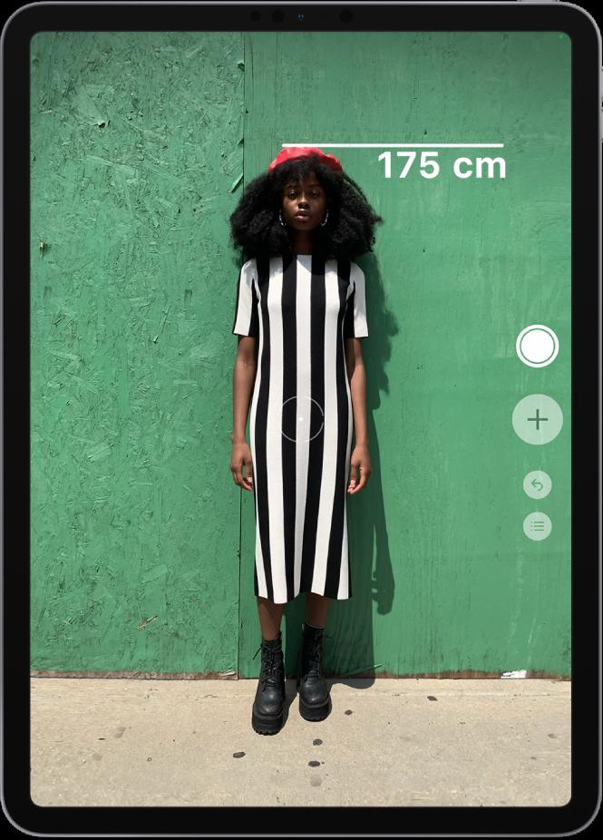 Une personne en train d'être mesurée, la taille s'affichant au-dessus de sa tête. Le bouton «Prendre une photo» est actif sur le bord droit, afin de prendre une photo de la mesure. L'indicateur vert «Caméra en cours d'utilisation» apparaît en haut à droite.