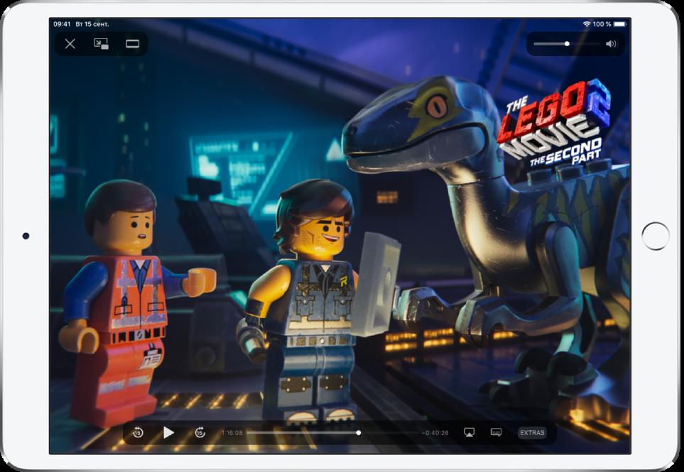 В приложении AppleTV воспроизводится фильм. На экране видны элементы управления воспроизведением.