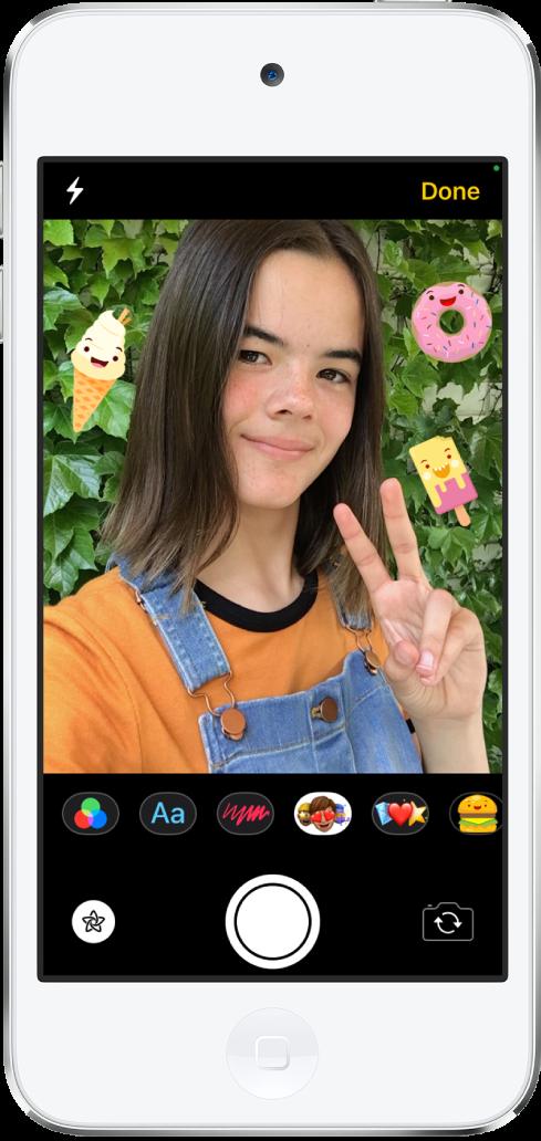 Het effectenscherm van Berichten. Boven in het scherm zie je het kader van de camera aan de voorkant. Rond het onderwerp in het kader bevinden zich iMessage-stickers. Onder het kader staan, van links naar rechts, de knoppen voor filters, tekst, vormen, memoji, emoji en de iMessage-app. Onder in het scherm staan, van links naar rechts, de effectenknop, de sluiterknop en de knop voor de camera aan de achterkant.