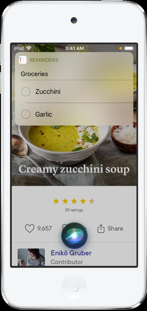 A Siri mostra uma lista de lembretes chamada Compras que contém abobrinha e alho. A lista aparece sobre uma receita de sopa de creme de abobrinha.