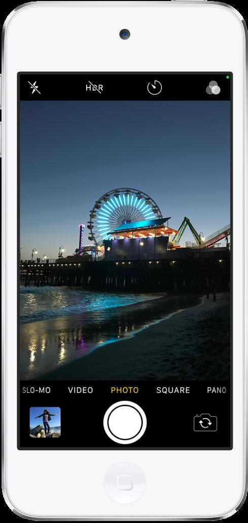 กล้องในโหมดรูปภาพ โดยมีโหมดอื่นๆ อยู่ทางซ้ายและทางขวาด้านล่างหน้าต่างแสดง ปุ่มต่างๆ สำหรับแฟลช, HDR, นาฬิกานับถอยหลัง และฟิลเตอร์ แสดงอยู่ที่ด้านบนสุดของหน้าจอ ปุ่มหน้าต่างแสดงรูปภาพและวิดีโออยู่ที่มุมซ้ายล่างสุด ปุ่มถ่ายรูปอยู่ที่ตรงกลางด้านล่างสุด และปุ่มตัวเลือกกล้องด้านหลังและด้านหน้าอยู่ที่มุมขวาล่างสุด