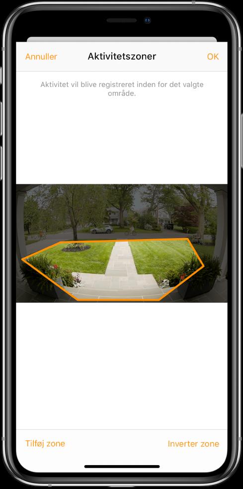 Skærm på iPhone, der viser en aktivitetszone med et billede taget af et dørklokkekamera. Aktivitetszonen omfatter terrassen og gangstien foran huset, men ikke gaden og indkørslen. Over billedet findes knapperne Annuller og OK. Knapperne Tilføj zone og Inverter zone er vist nedenfor.