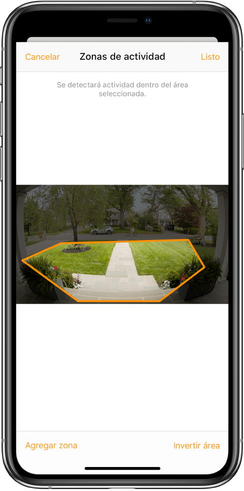 """Pantalla del iPhone mostrando una zona de actividad dentro de una imagen tomada por la cámara del timbre de la puerta principal. La zona de actividad comprende el porche y la entrada, pero no incluye la calle ni la entrada del garage. Los botones Listo y Cancelar están arriba de la imagen. Los botones """"Agregar zona"""" y """"Invertir área"""" están debajo."""