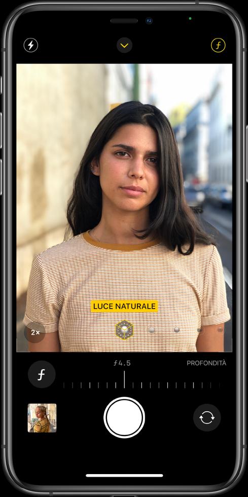 """Una schermata di Fotocamera in modalità Ritratto. Il pulsante per la regolazione della profondità è selezionato nell'angolo in alto a destra dello schermo. Nel visualizzatore, un riquadro mostra che l'opzione """"Illuminazione ritratto"""" è impostata su """"Luce naturale""""; è disponibile un cursore per modificare l'opzione d'illuminazione. Sotto il visualizzatore, è presente un cursore per regolare il controllo della profondità."""